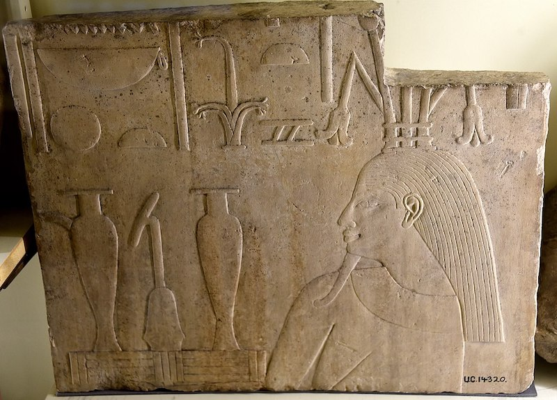 Bas relief of bearded ancient Egyptian man with two tall vases and other symbols.