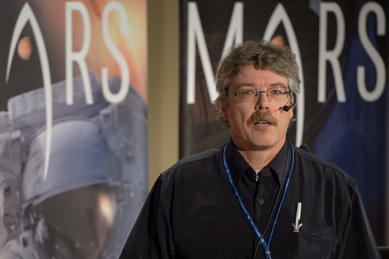Man with microphone and blue lanyard over black shirt, with the word Mars behind him in large letters.