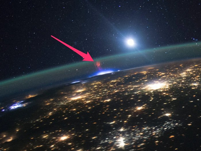 Orbital view of Earth with city lights and short red streaks above a glowing patch in the atmosphere, and moon and stars in distance.