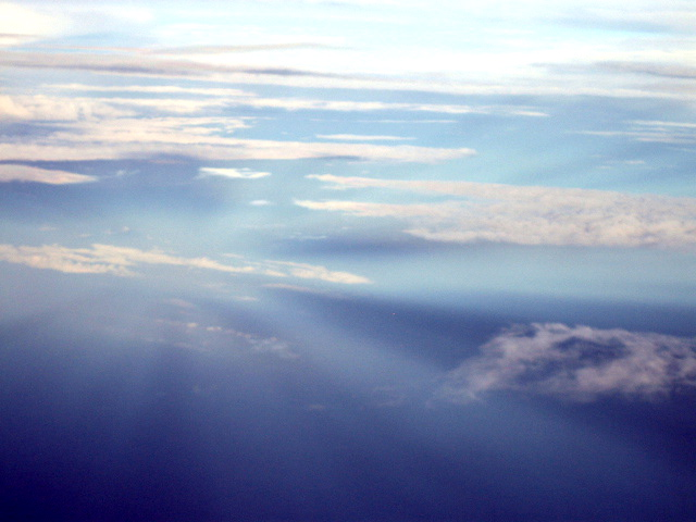 Rays converging from above and below point of view in cloudy sky.