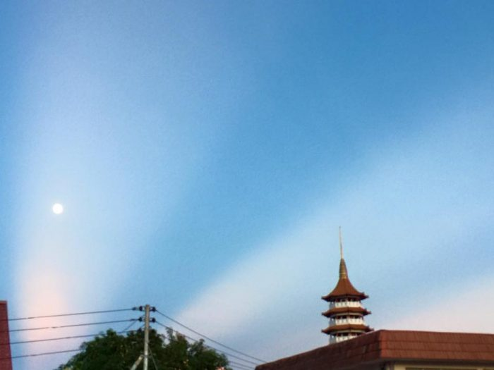 Wide white rays in a blue sky with small full moon halfway up in the sky and a pagoda on the right.