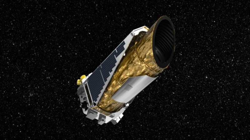 Cylindrical gold-foil-covered telescope satellite in space with stars in background.