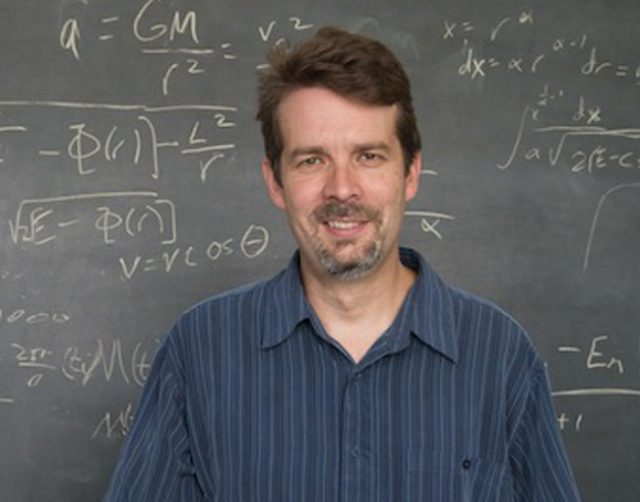 Dark-haired bearded man standing in front of a blackboard with mathematical formulas.