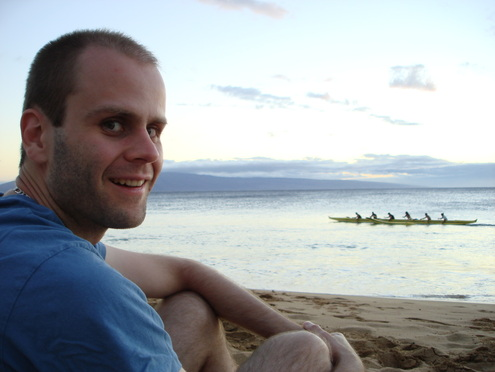 Smiling, short-haired man in blue shirt with kayak on lake in the distance.