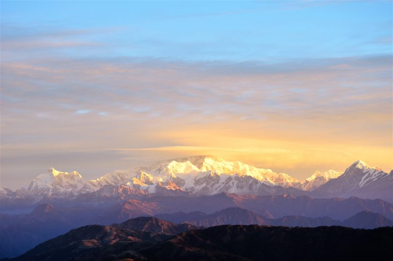 Dawn sky over wide panorama of jagged mountaintops.