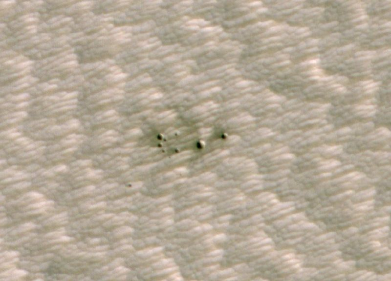 A cluster of small meteor craters on terrain with linear features.