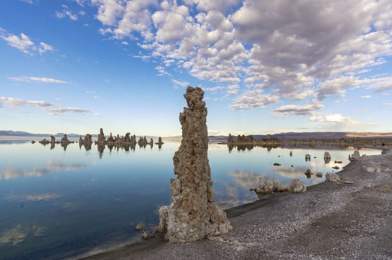 Lake in bleak landscape with tall, rough pillars around shoreline and blue sky with clouds.