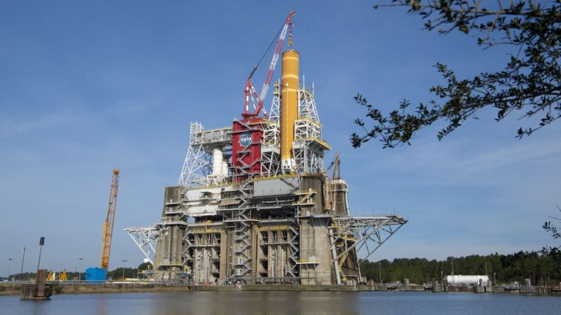 Tall orange rocket standing on high concrete platform with a lot of metal scaffolding.
