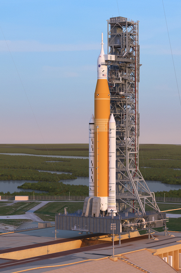 Tall orange rocket with 2 shorter auxiliary rockets on the sides at launch tower.