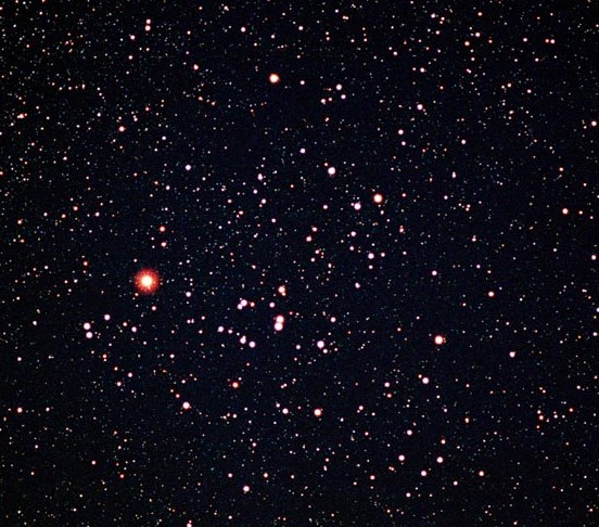 Dense star field with large bright orange-red star.