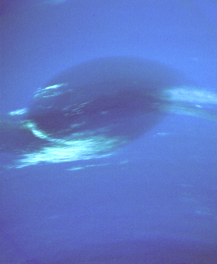 Large dark oval spot with white streaky filaments around it, on blue background.