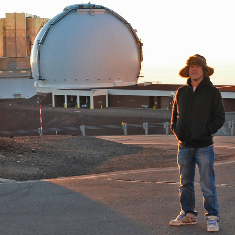 Man in hat and jacket standing outside near spherical observatory dome.