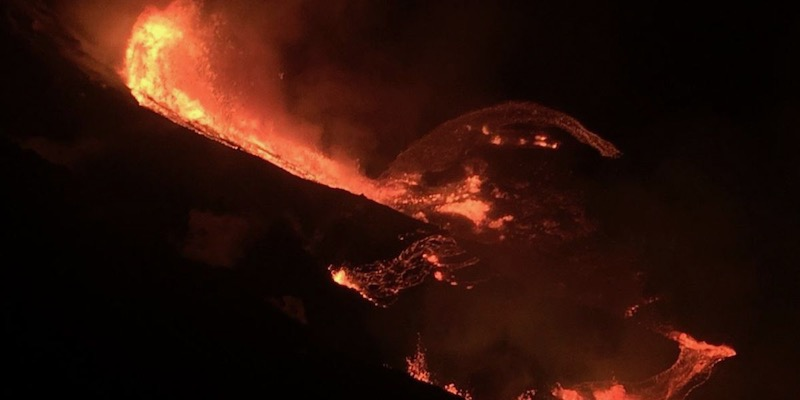 Night photo of lava flowing down a mountainside, into a lava lake.