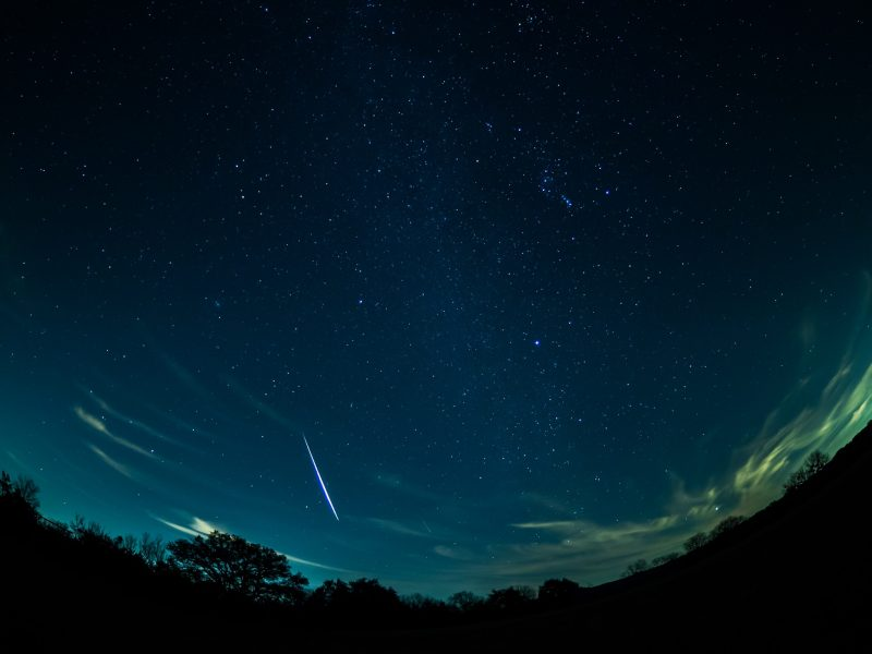 Panorama of sky with stars and a brilliant white streak.
