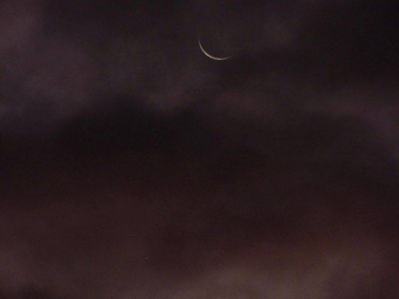 Large but very thin crescent moon over fuzzy clouds.