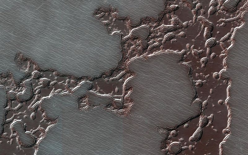 Dark reddish splotch-like patches of frozen water ice are pictured on a striated surface.