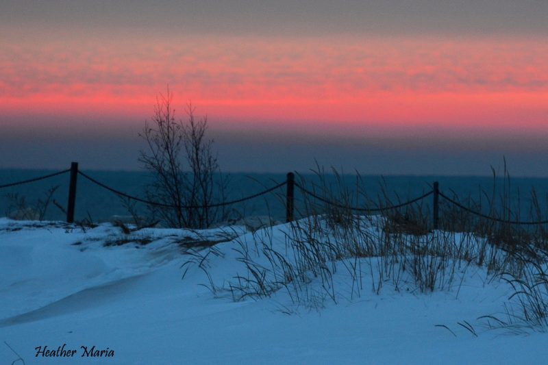 Bright pink-orange stripe across the sky over white dunes with sparse grass on them.