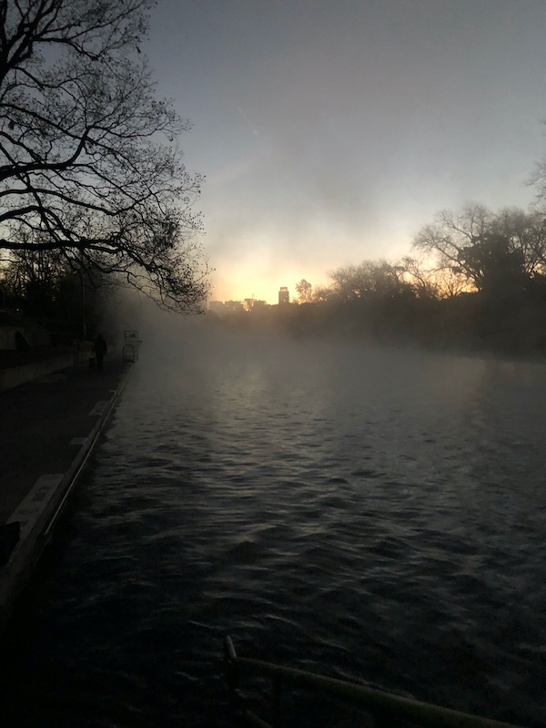 Fuzzy dawn over body of water lined by bare trees.