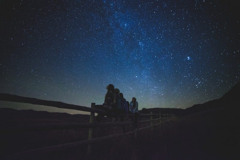 Children sit on a fence and gaze up at the stars and Milky Way.