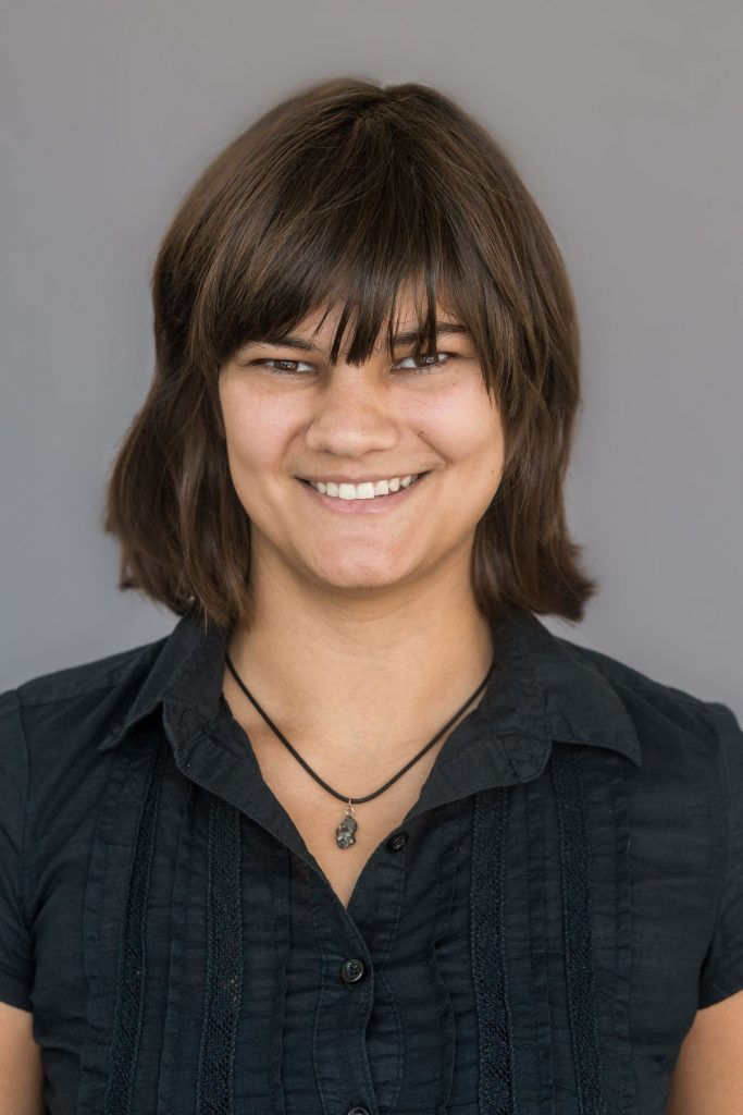 Smiling woman with bangs and necklace, on plain background.