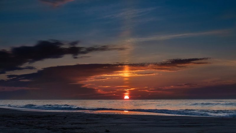 Orange sun rising over the ocean, with tall sun pillar above, brghter and dimmer as it passes through horizontal clouds.