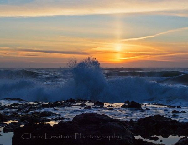 Red and yellow clouds above crashing waves on rocky coast with pillar of light on horizon.