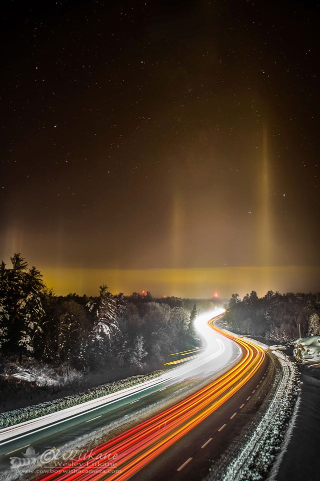 Two light pillars fading into dark sky over divided highway streaked with white and red lights.