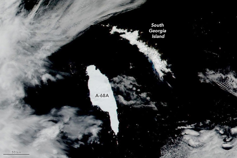 Orbital view with long white patch close to smaller gray patch on dark sea.