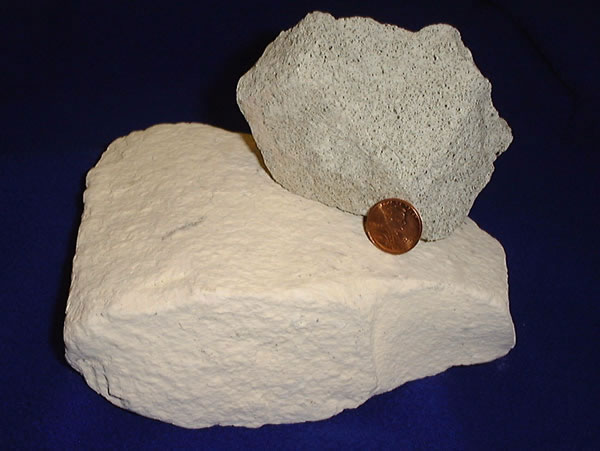 Chunks of porous white rock with a penny for scale.