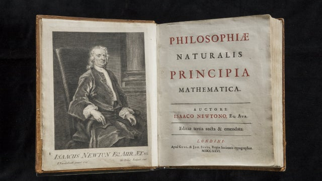 An antique book opened to a picture of a man and a title page in Latin.