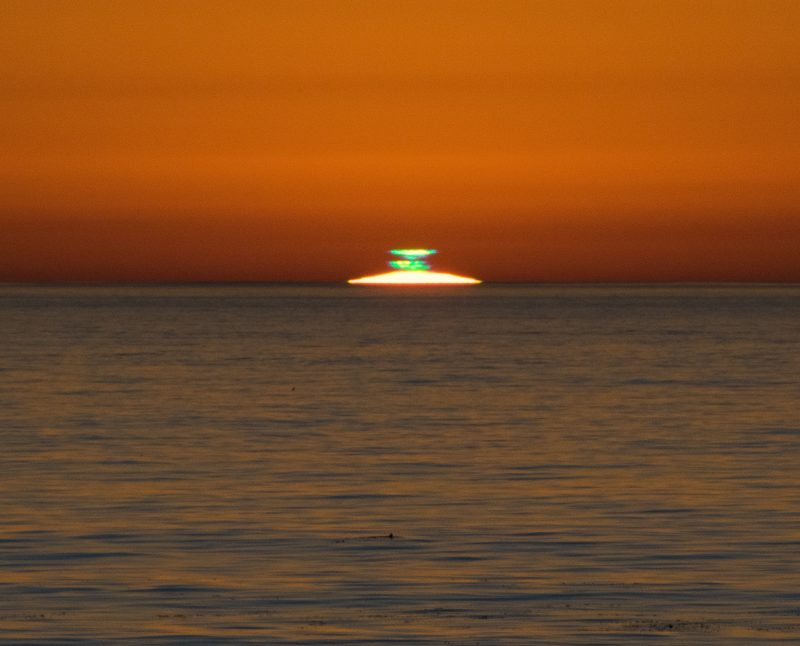 Sliver of sun visible above ocean horizon with glowing green smudges above it.