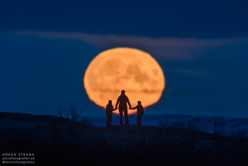 Silhouette of woman holding hands with two children against enormous yellow moon near horizon.
