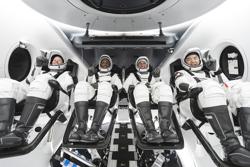 Four men wearing white SpaceX spacesuits, strapped into their seats and ready for launch.