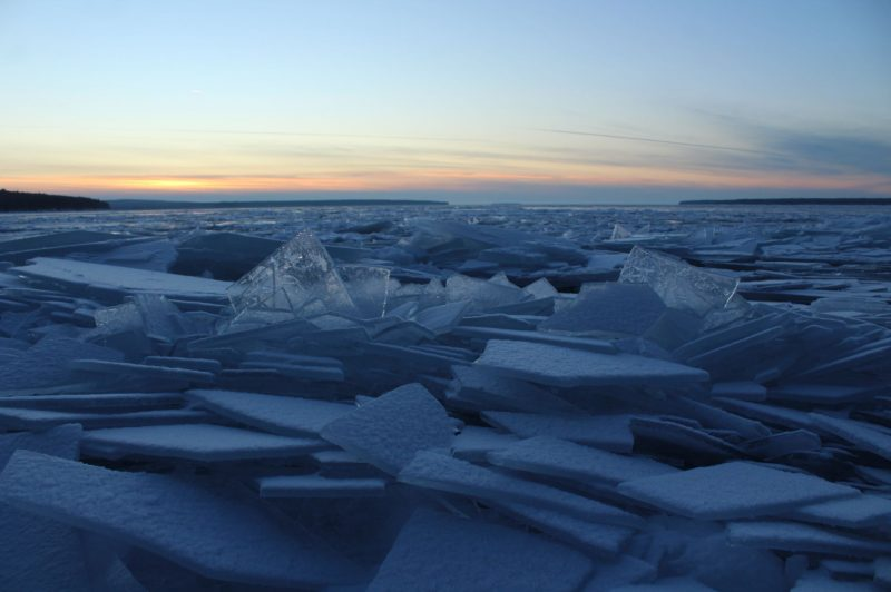 Slabs of ice at all angles piled up on each other under sunset sky.