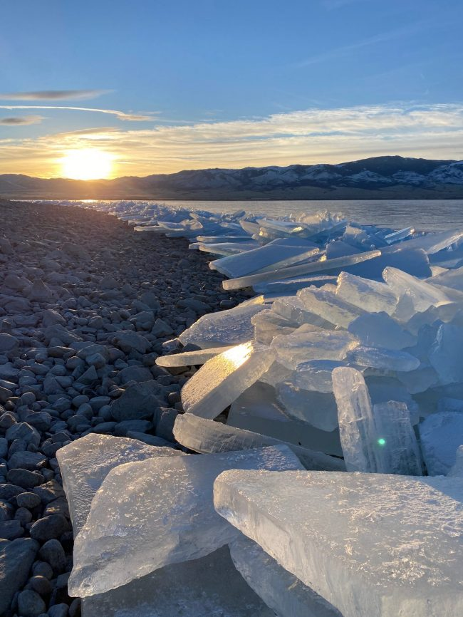 Slabs of ice piled up on lakeshore with lowering sun glinting off them.