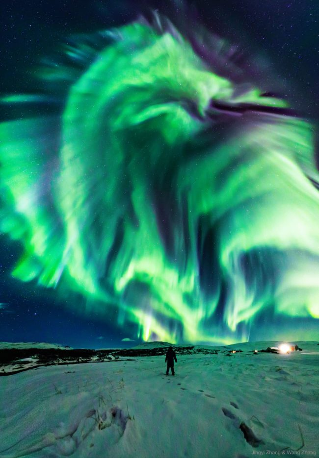 Many concentric waves of green light seen from below forming a dragon-like image.