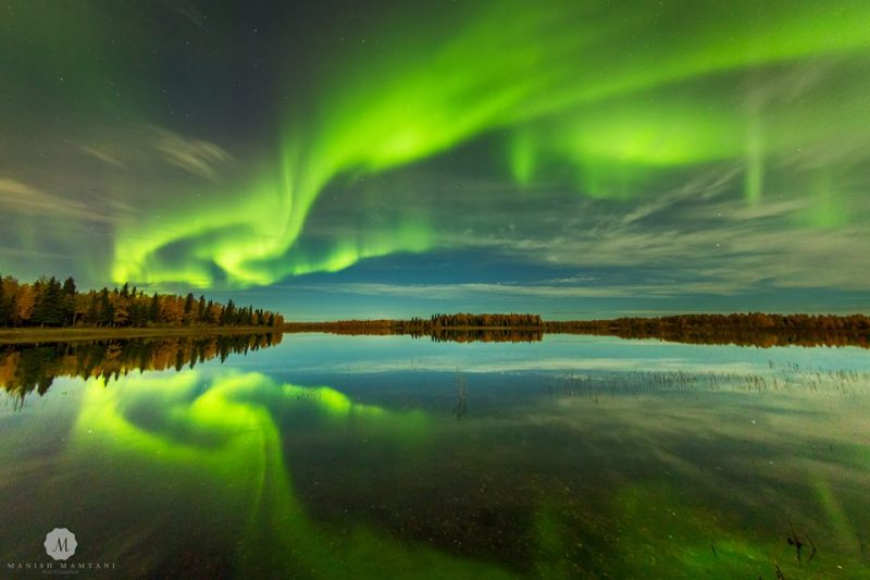 Glowing aurora like swirling green vertical curtains in sky and reflected in calm lake.