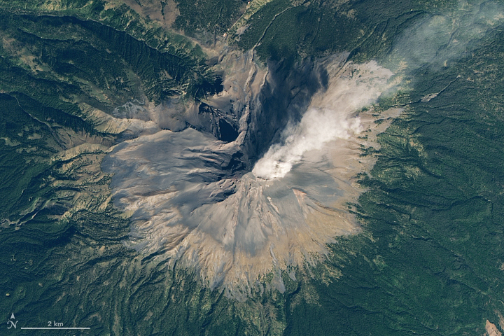 View from orbit of a round, barren mountain puffing out a plume of steam, ash and rock fragments.