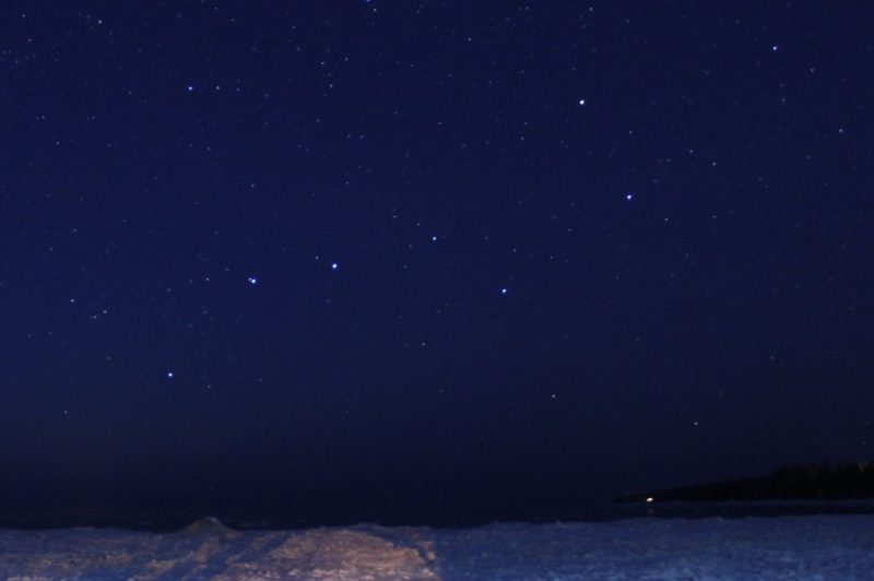 Star field with prominent Big Dipper stars in deep blue sky over icy lake.