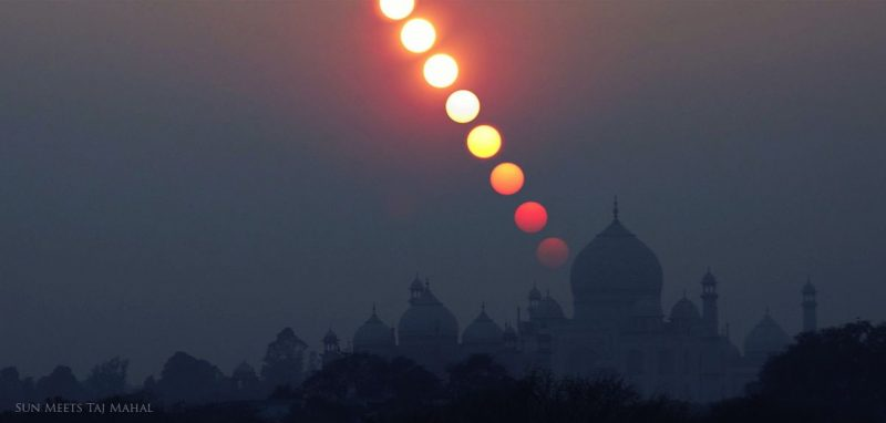Multiple suns, dimming, in a nearly vertical line over the domes of the sihouetted Taj Mahal.