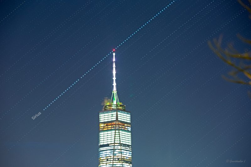 Line of small white dots across sky touching red light on top of brightly illuminated tower.