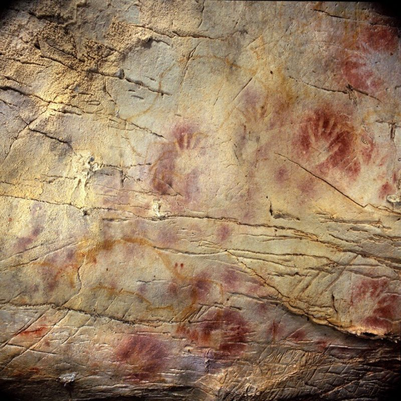 Handprints surrounded by red on a rock wall.